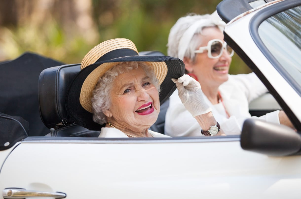 Editorial photography shot of two elderly ladies in white in a white car