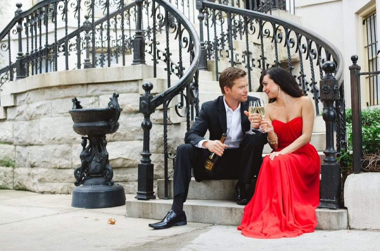 Engagement photography shot of couple with drinks on staircase