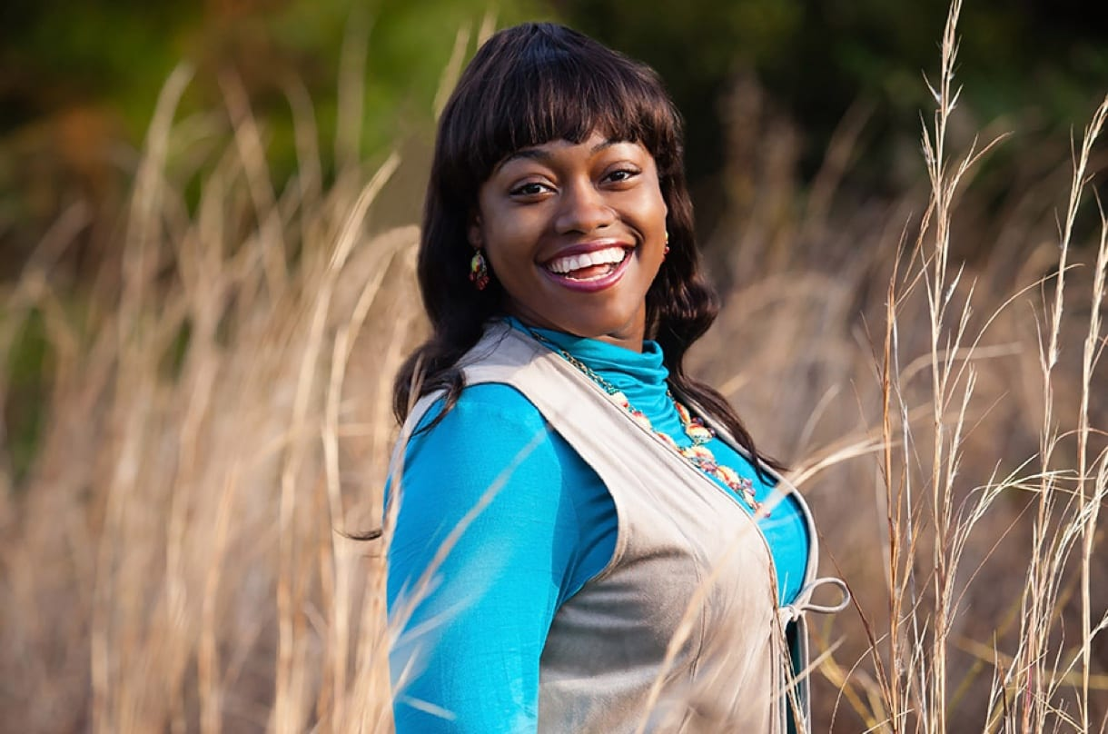 Portrait photography shot of a young black woman smiling in a field