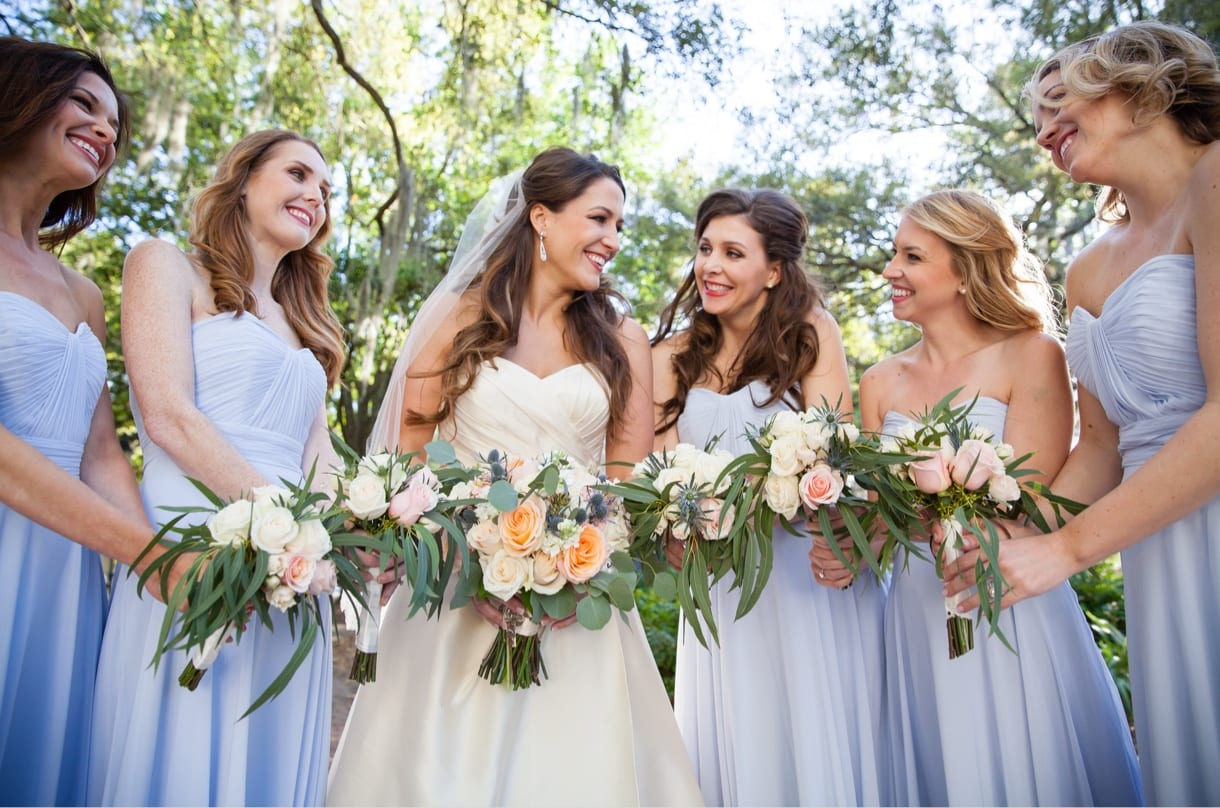 Wedding photography shot of bride & bridesmaids holding flowers